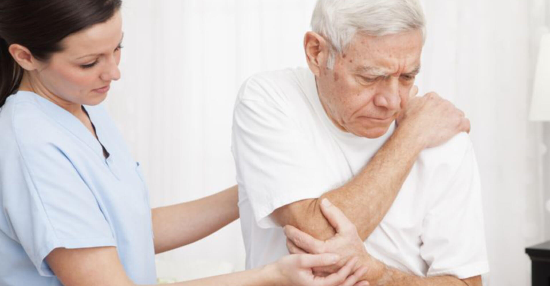 nurse comforting an old man who is ill